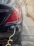 Power supply for hybrid electric car charging battery.Close up of power supply plugged into an electric car being charged.  royalty free stock images