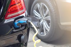 Power supply for hybrid electric car charging battery.Close up of power supply plugged into an electric car being charged.  stock photo