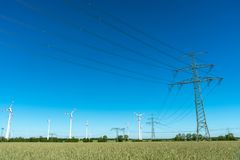 Power supply lines and wind turbines Stock Photos