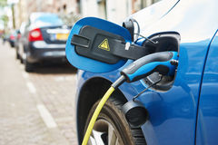 Power supply plugged into an electric car during charging stock images