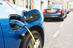 Power supply plugged into an electric car during charging royalty free stock images
