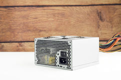 Power Supply. On White Table With Wooden Background Stock Image