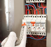 Power switch. Electrician switching the power switch with protecting gloves stock image