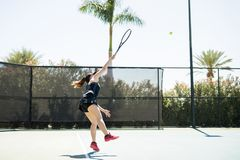 Power tennis serve. Female tennis player hitting the ball from base line on tennis court on a summer day Stock Images