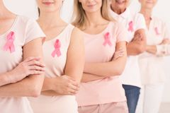 Power to fight breast cancer. The power to fight breast cancer, women wearing pink ribbons for breast cancer campaign on white background royalty free stock photography