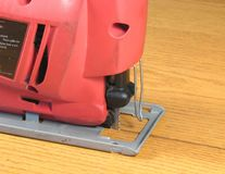 Power tool. Closeup of jigsaw on wood table Royalty Free Stock Photography