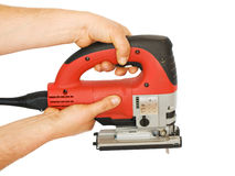 Power tool. Two hands are holding a electric saw Royalty Free Stock Photography