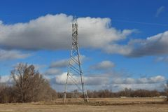 Power Tower in a field with blue sky and white clouds. stock photos