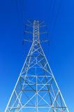 Power Tower LA CA Vertical. Electrical Power Tower with high tension lines. Low angle perspective of superstructure against cloudless blue sky. Vertical Royalty Free Stock Image