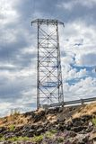 Power tower under puffy white clouds. Storm clouds over power lines and roadside Stock Image