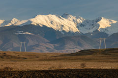 Power Towers and Mountains. High voltage power towers and lines with snowy peaks of Fagaras Mountains in background a a plowed field in foreground. Horizontal stock photo