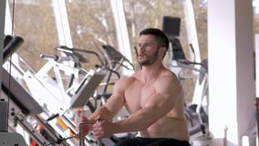 Power training, bodybuilder male with bare-chested doing muscle building workout on traction simulator while working on. Power training, nude bodybuilder male stock footage