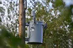 Power Transformer and Power Pole. An image of a grey power transformer on a power pole surrounded by trees royalty free stock photography