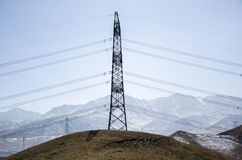 Power transmission at the foot of snow mountain Stock Photo