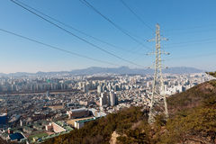 Power transmission line pole and wires on a hill over a city. In a sunny day Royalty Free Stock Images