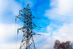 Power transmission line tower against blue sky and clowd with sn. Ow-covered high-voltage insulators. Winter time Royalty Free Stock Photo