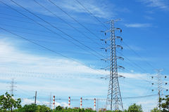 Power transmission line tower. Against blue sky with power plant behind stock images