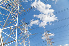 Power transmission lines against blue sky Stock Images
