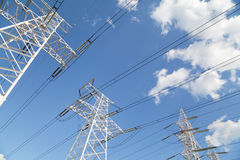 Power transmission lines against blue sky Stock Image