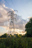 Power transmission tower on background greenery on a summer evening Stock Image