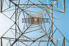 Power transmission tower closeup. Power transmission tower against a blue sky,upward view of the structure background royalty free stock photo