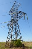 Power transmission tower with electricity transmission lines in. The midst of a spring green field royalty free stock image