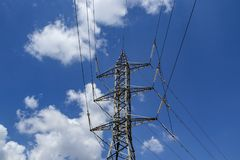 Power transmission tower. High voltage electric power transmission tower with wires against blue sky and clouds background stock image
