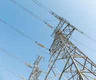 Power transmission tower over blue sky. Upward view royalty free stock photo