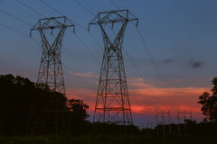 power transmission tower silhouetted against sunset glow royalty free stock image