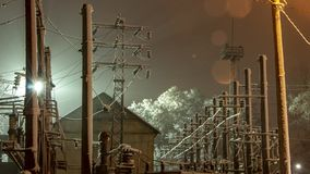 Power transmission towers and their silhouettes against the background of the night sky in the industrial urban area. Illuminated by spotlights royalty free stock image
