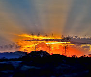 A Power Trip. As the sun sets in its glory, electric posts and clouds portray the power of energy, as they keep the sun rays in check Royalty Free Stock Image