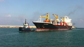 Power tug and containership. Big container pulled by tug in the port of Valencia stock video