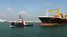 Power tug pulling of containership in the port of Valencia. Containership entering in the port of Valencia helped by tug in Spain stock video footage