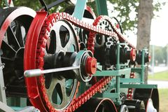 Power unit with wheels, flywheels and chain. Agricultural mechanism for harvest processing. Heavy engineering. Metal construction. stock images