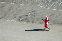 Power walking on beach. A mature woman in a pink track suit power walking on the beach Stock Images
