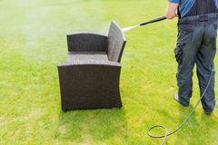 Power washing garden furniture. Made of rattan stock images