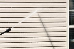 Power washing. House wall siding cleaning with high pressure water jet. Power washing. House wall vinyl siding cleaning with high pressure water jet royalty free stock photography