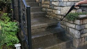 Power washing on outdoor concrete staircase with black rod iron railings and stone work stock footage