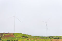 Power of wind turbine generating electricity clean energy with m. Ist fog background.Global ecology.Clean energy concept save the world stock photography