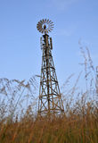 Power Windmill & Cell Antennas. Power Windmill with Wireless Telecommunication Antennas in Overgrown Field Stock Images