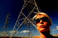 Power Woman. Woman in front of high voltage power lines Royalty Free Stock Images