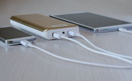 Powerbank charges the smartphone and tablet computer stock photography