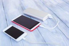 Powerbank charging two smartphones Stock Images