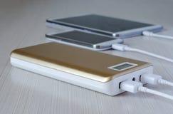 Powerbank laddar smartphone- och minnestavladatoren royaltyfri fotografi