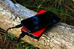 Powerbank och smartphone på en journal Fotografering för Bildbyråer