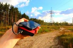 Powerbank und Smartphone in einer männlichen Hand Stockbilder