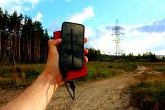 Powerbank und Smartphone in einer männlichen Hand Lizenzfreie Stockfotografie