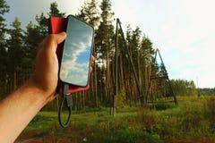Powerbank und Smartphone in einer männlichen Hand Lizenzfreies Stockfoto