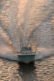 Powerboat at sunset. Front overhead view of powerboat racing across the water at sunset Royalty Free Stock Photo