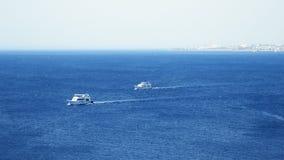 Powerboats och skepp s seglar längs det tropiska havet Fotografering för Bildbyråer